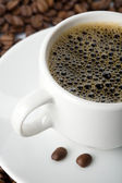 White cup of coffee and roasted beans — Stock Photo