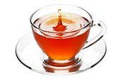 Chapoteo de té en la taza de cristal aislado — Foto de Stock