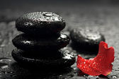 Spa stones and rose petals over black background — Stock Photo