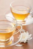 Šálek zeleného čaje a bílý květ — Stock fotografie