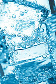 Ice cube in water bubbles — Stock Photo