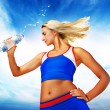 Stock Photo: Young woman drinking water after fitness exercise