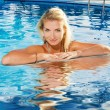 Beautiful blond woman relaxing in a pool — Stock Photo
