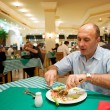 Man eating in a reastaurant - Stock Photo