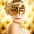 Stock Photo: Beautiful woman in carnival mask over abstract background