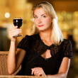 Beautiful young woman drinking red wine in a restaurant - Stock Photo