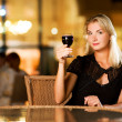 Beautiful young woman drinking red wine in a restaurant — Stock Photo #4744232