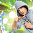 Stock Photo: Cool looking man in a hood over abstract graffiti background
