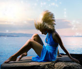 Sexy young woman flapping her blond hair near the ocean — Stock fotografie