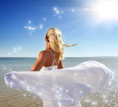 Blond woman with white shawl relaxing near the sea — Stock Photo