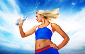 Young woman drinking water after fitness exercise — Stock Photo