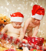 Two adorable toddlers in Christmas hats packing presents — Stock Photo
