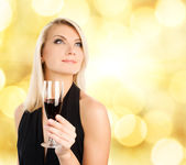 Beautiful young woman with a glass of wine over abstract blurred — Stock Photo