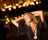 Beautiful young woman dancing late at night — Stock Photo