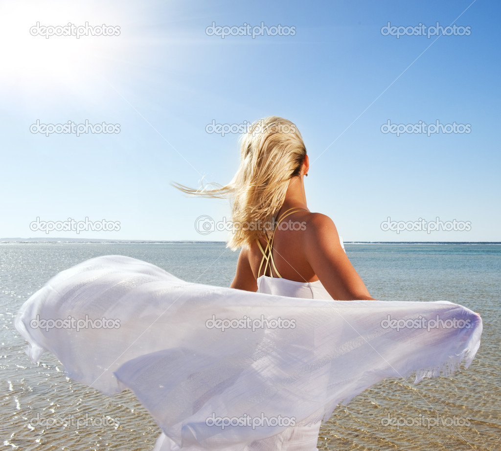 Blond woman with white shawl relaxing near the sea — Stock Photo #4744281