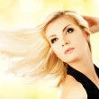 Beautiful blond woman over abstract golden background — Stock Photo #4783672