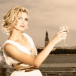 Beautiful blond girl drinks champagne near the river at sunset t — Stock Photo #4783681