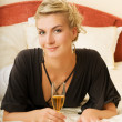 Beautiful young lady lying in a bed with a glass of champagne — Stockfoto