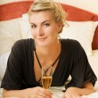 Beautiful young lady lying in a bed with a glass of champagne — ストック写真