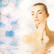 Beautiful young woman in water massaging her face — Stock Photo