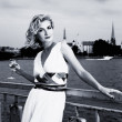 Beautiful blond girl drinks champagne near the river — Stock Photo