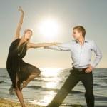 美丽的年轻夫妇在日落时的海滩上跳舞探戈 — 图库照片