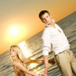 Stock Photo: Young couple dancing near the ocean at sunset
