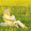 Beautiful young woman sitting in a flower field — Stock Photo #4783946