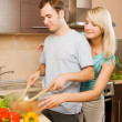 Stock Photo: Young couple making vegetable salad in the kitchen