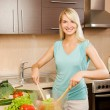 Beautiful young woman mixing vegetable salad in a glass bowl — Stock Photo