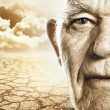 Foto Stock: Elderly man's face over dry desert land background