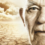 Elderly man's face over dry desert land background — Zdjęcie stockowe