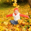Beautiful little girl with autumn leaves outdoors — Stock Photo