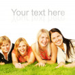 Group of happy friends lying on a green grass — Stock Photo