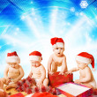 Group of adorable toddlers in Christmas hats packing presents — Stock Photo