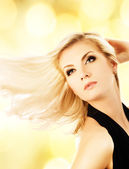 Beautiful blond woman over abstract golden background — Stock Photo