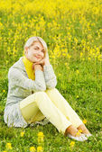 Beautiful young woman sitting in a flower field — Stock Photo