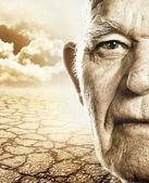 Elderly man's face over dry desert land background — Stock Photo