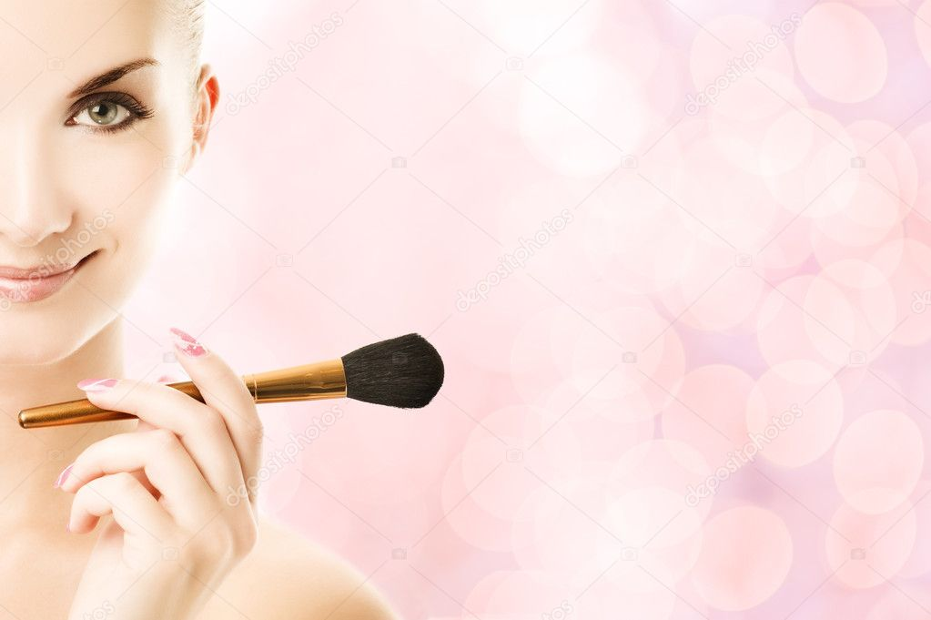 Lovely young woman with a make-up brush  Stock Photo #4783949