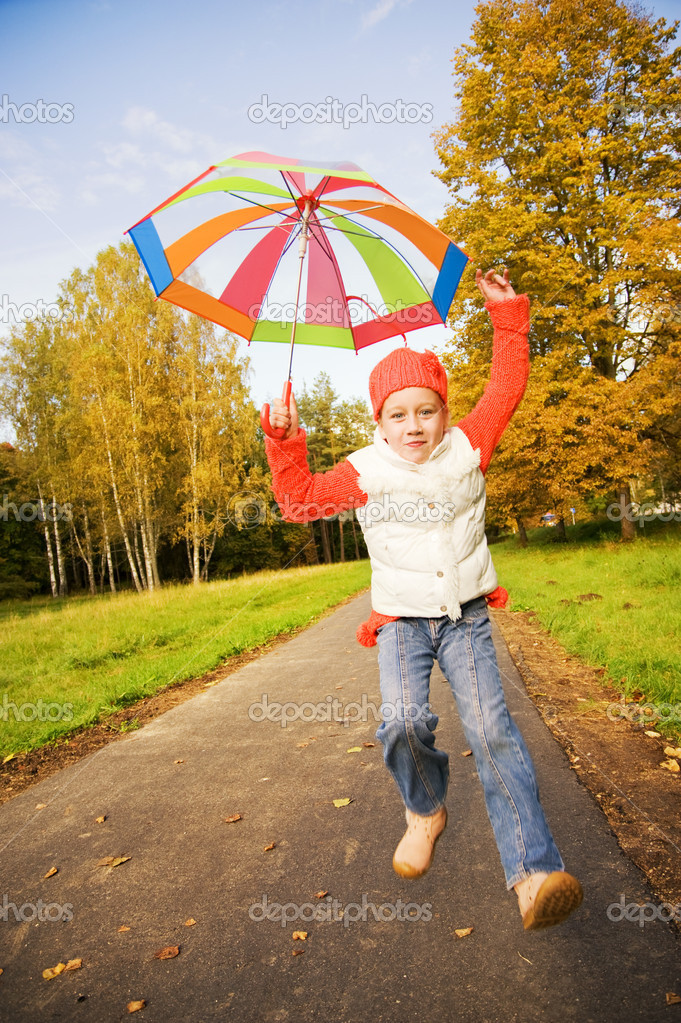 Beautiful little girl with umbrella in a forest — Stock Photo #4784119
