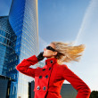 Beautiful young blond talks on the phone. Modern building behind — Stock Photo