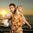 Young couple dancing near the ocean at sunset — Stock Photo