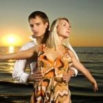 jovem casal dançando perto do mar ao pôr do sol — Foto Stock