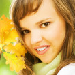 Beautiful romantic brunette with golden autumn leaf close-up por — Stock Photo