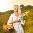 Beautiful young woman with a basket full of fresh baked bread — Stock Photo