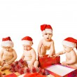 Group of adorable toddlers in Christmas hats packing presents. I — Stock Photo