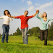 Foto Stock: Three happy friends running outdoors