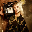 Beautiful female soldier with a retro music player - Stock Photo