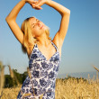 Beautiful blond girl stretching in the wheat field — Stock Photo #4791172