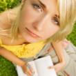 Sad young girl sitting oudoors on a grass and reading book - 